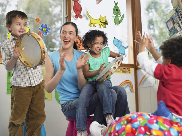 Woman with children clapping and playing with tambourines.