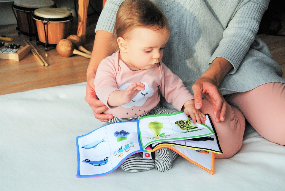 Baby Reading a book with parent