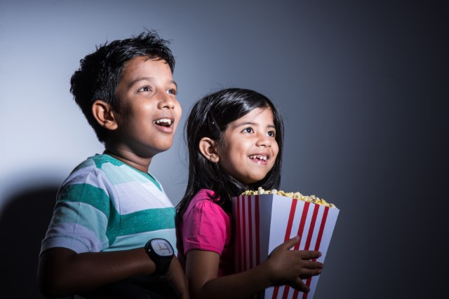 Boy and a girl watching a film while holding a popcorn tub