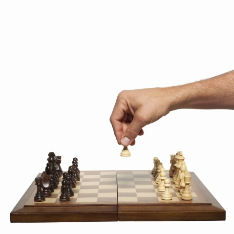 Hand moving a chess piece on board.