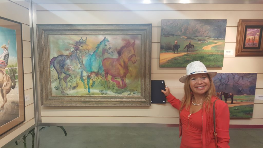 Woman wearing red top and white hat stands next to paintings, including a painting of horses galloping.