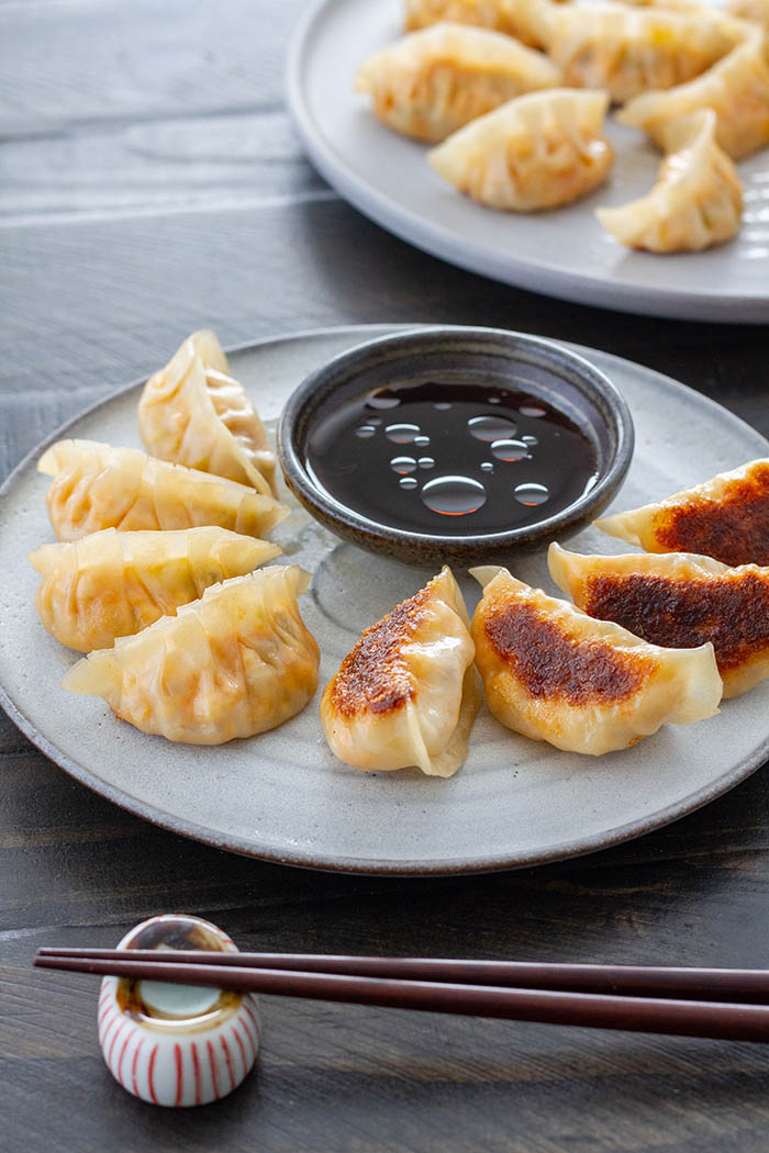 Gyoza arranged on a plate with dipping sauce and chopsticks.