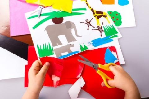 Child cutting paper for craft
