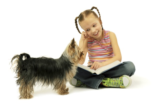 Young girl with open book on her lap with a small dog looking on