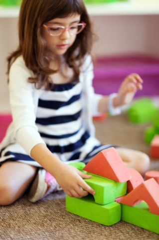 Girl playing with toys & reading books