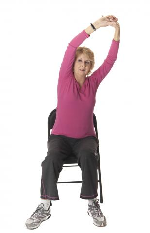 Women sitting on chair stretches arms over head.