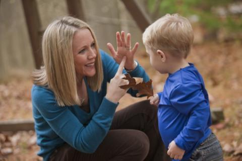 woman using american sign language signs with young child