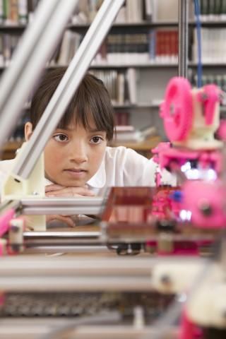A girl watching a 3D printer operate