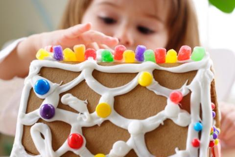 Child decorating a gingerbread house