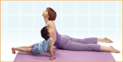 Teacher and child exercising Yoga