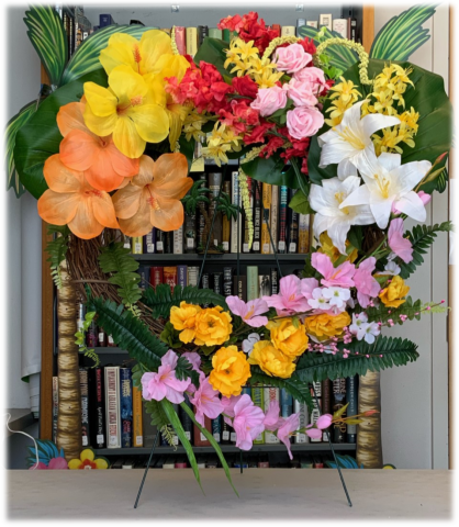 Image of a tropical floral wreath in the shape of a heart with many bright & colorful flowers.