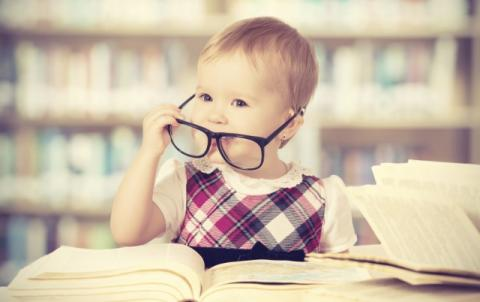 Toddler pulls off black rimmed glasses while sitting behind a big open book.