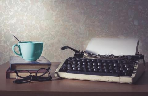 Image of typewriter and blue cup on top of a book