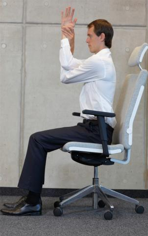 Man sitting in chair stretching arm.