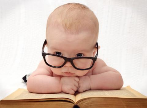 Baby wearing dark rimmed glasses leans over big open book.