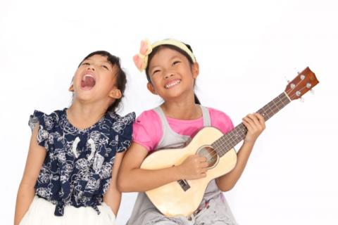 Girl sings next to girl playing guitar.